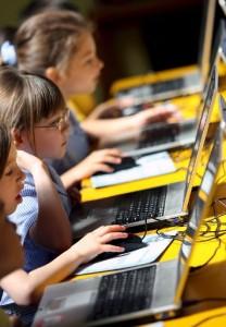 niñas portatil escriben 208x300 La tecnología, las redes sociales y los SMS mejoran la escritura de los niños