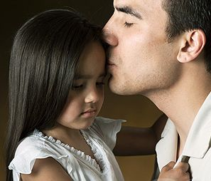 padre besando hija triste